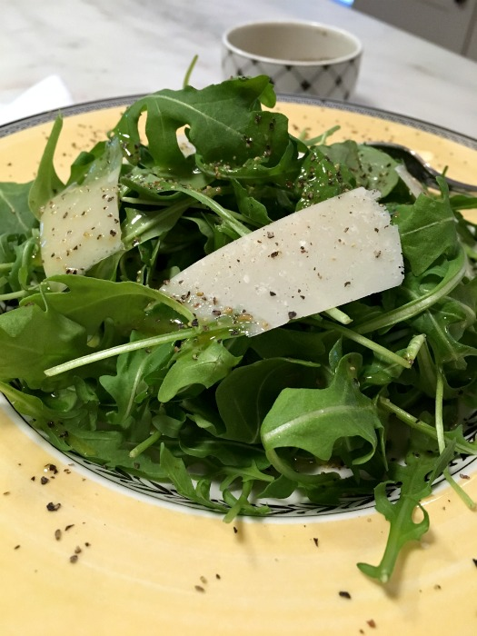 Top over arugula with fresh parmesan
